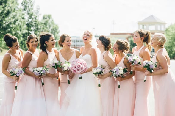 Photo of a bridal party with bouquets