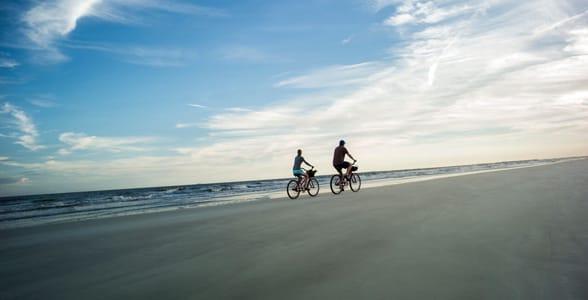 Photo of a couple biking on the beach at Hilton Head Island