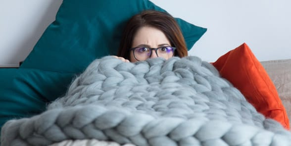 Photo of a woman hiding under blankets