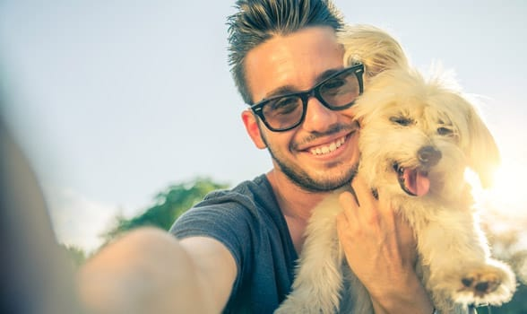 Photo of a man taking a selfie with a dog