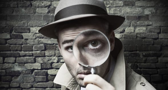 Photo of a man looking through a magnifying glass