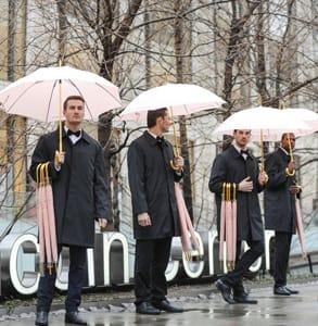 Photo of manservants holding pink umbrellas