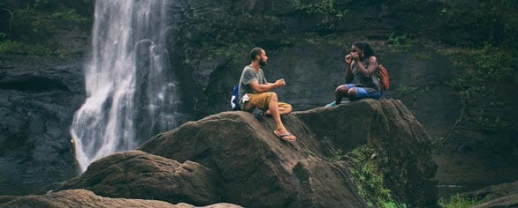 Screenshot of two people talking by a waterfall