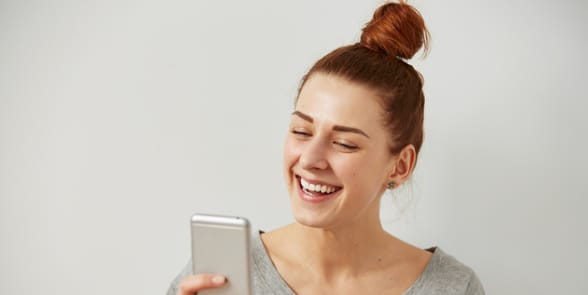 Photo of a woman holding a cellphone and laughing
