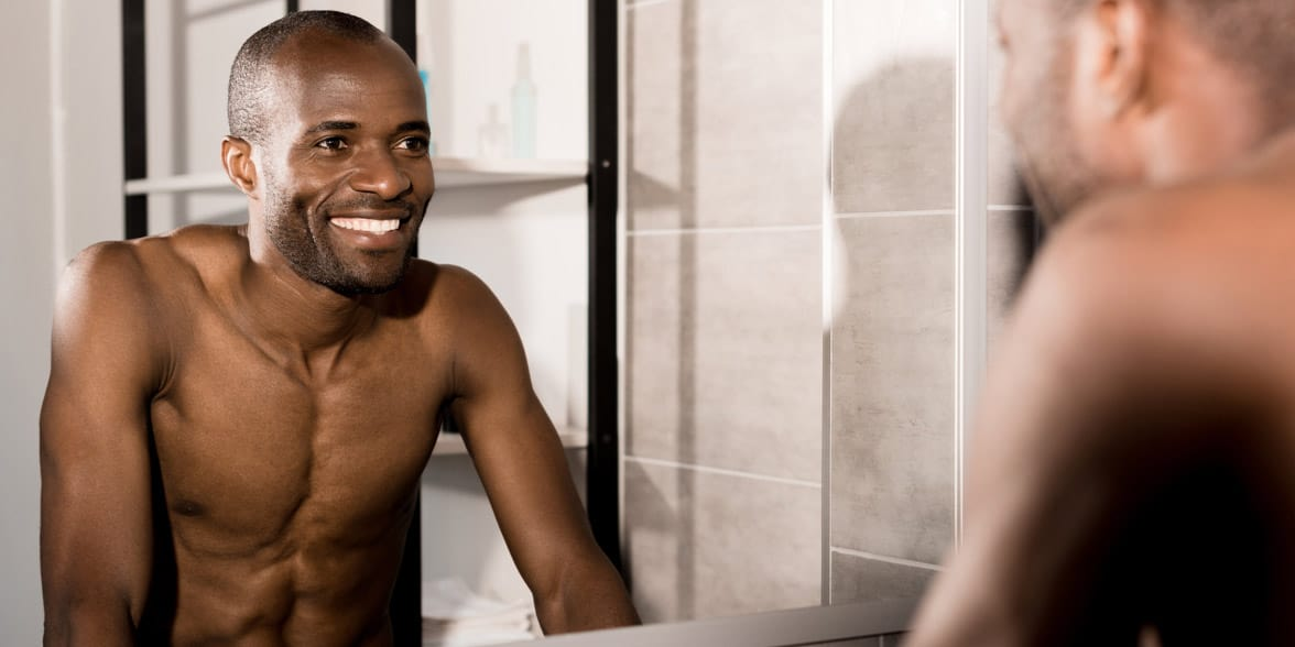 Photo of a man smiling at himself in the mirror
