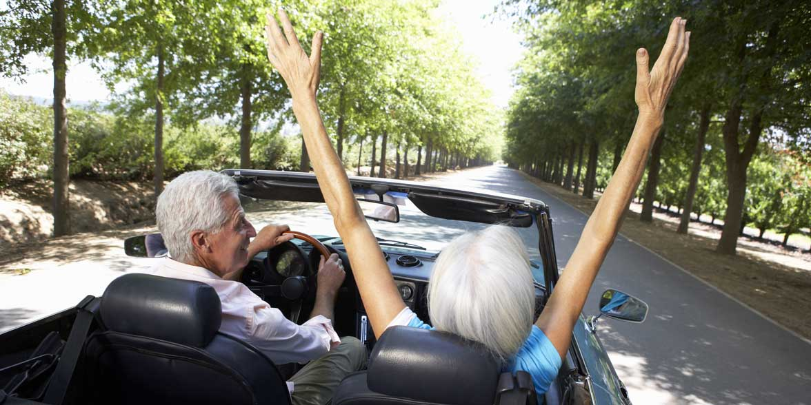 Photo of two mature people in a convertible
