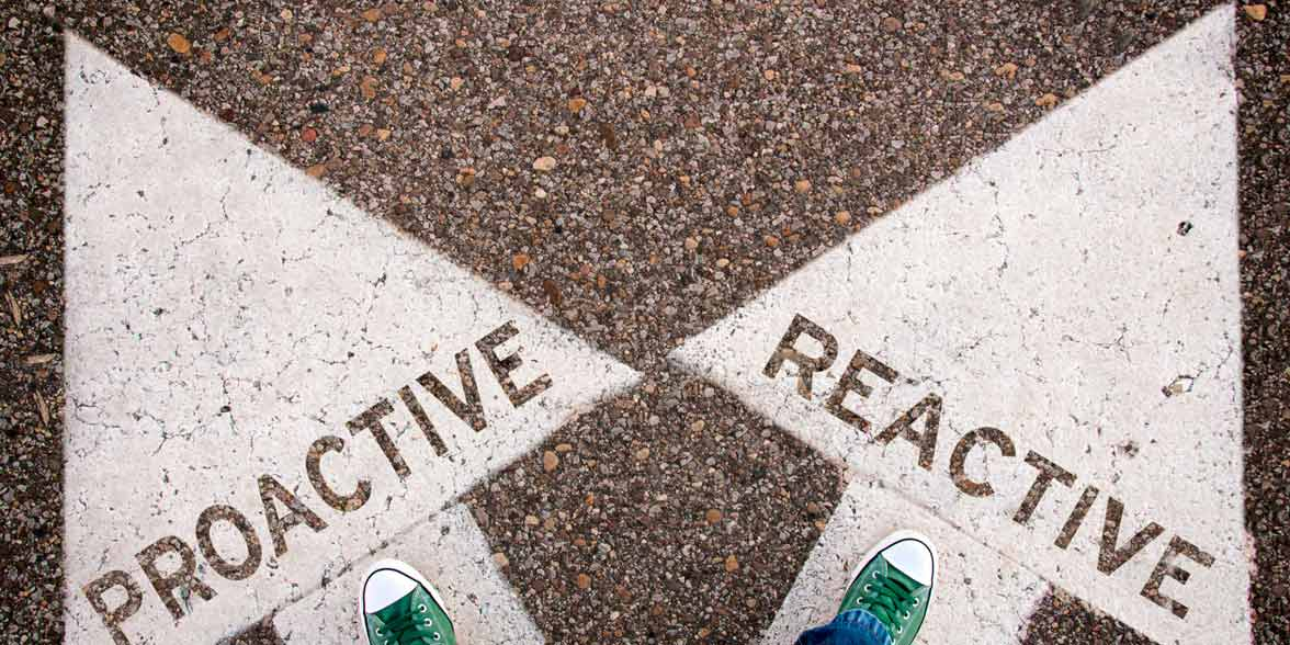 Photo of proactive and reactive written on a road