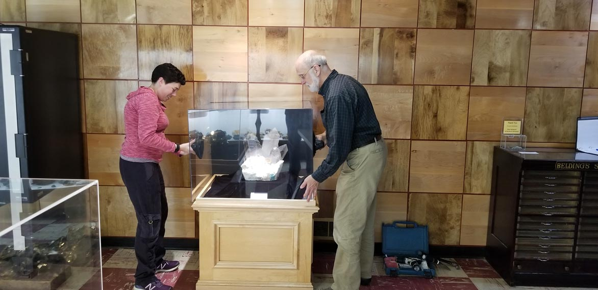 Photo of two staff members installing an exhibit at the Rice Museum