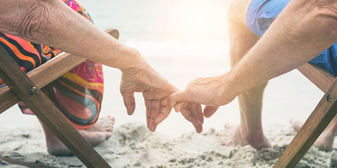 Photo of a couple holding hands at the beach