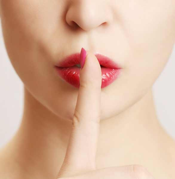 Photo of a woman holding a finger to her lips