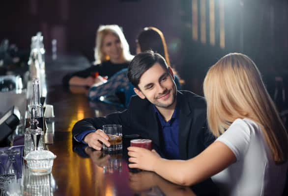 Photo of a couple flirting at a bar
