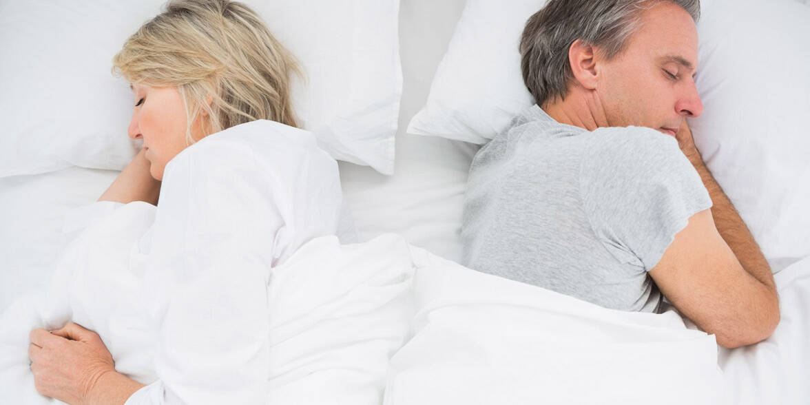 Photo of a sad couple in bed