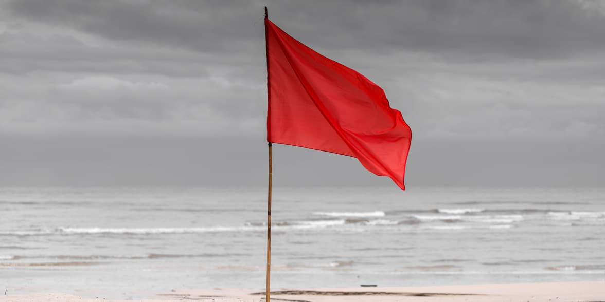 Photo of a red flag on a beach