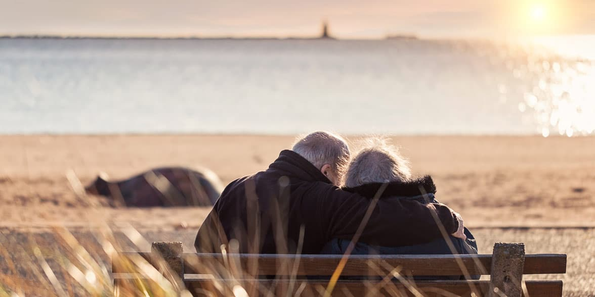 Photo of an older couple on the beach
