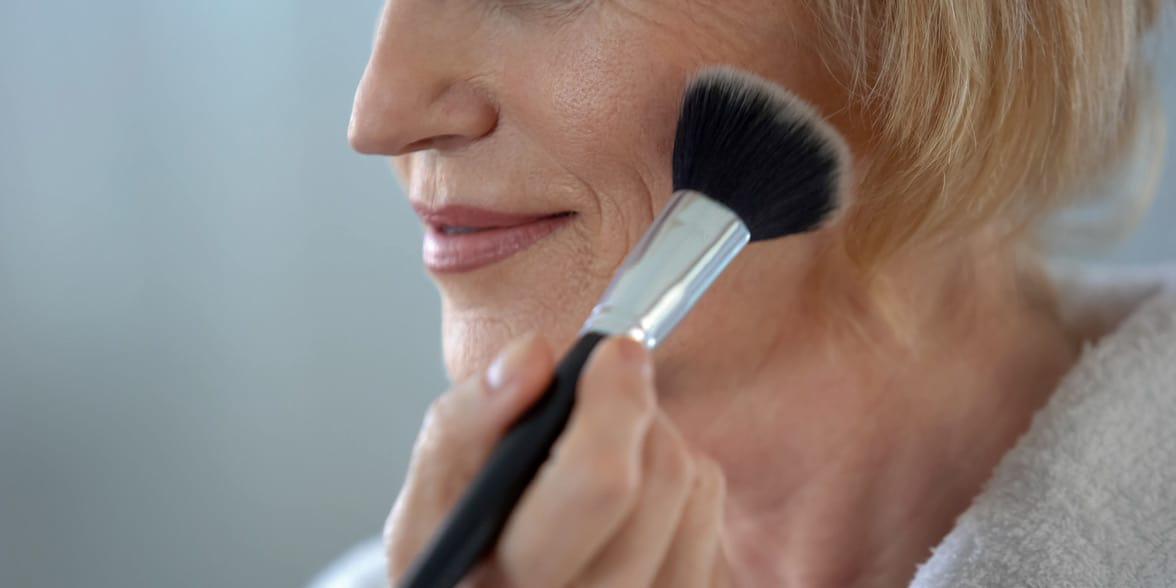 Photo of a woman putting on makeup