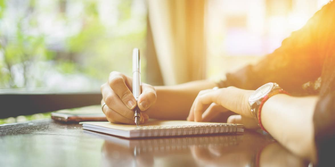 Photo of man writing in notebook