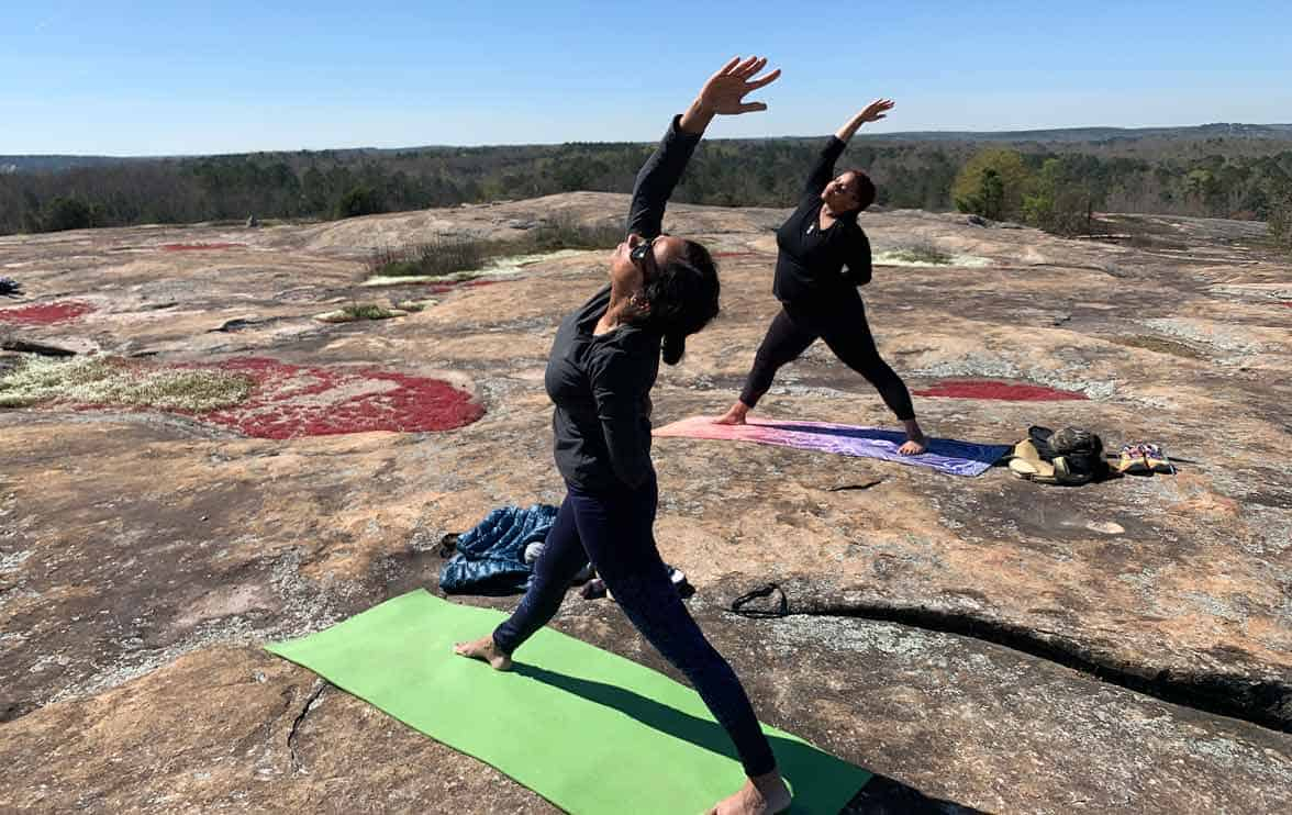 Photo of two people practicing yoga on Arabia Mountain